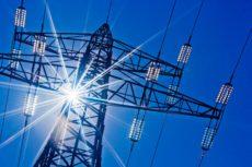 Ein Hochspannungsmasten für Strom vor blauem Himmel und Sonnenstrahlen